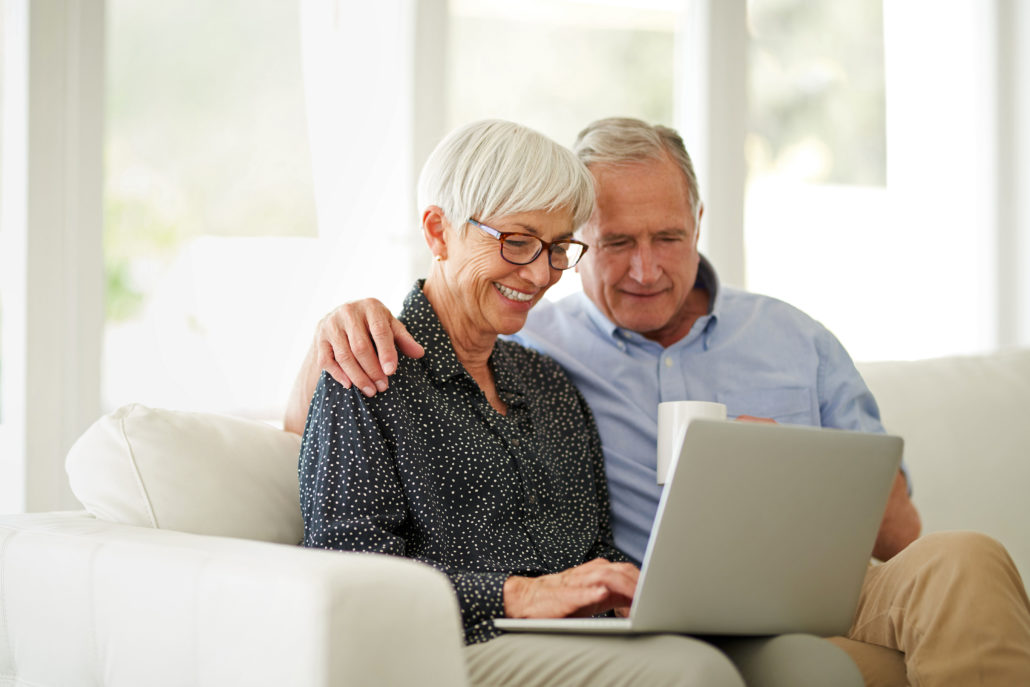 Cropped shot of an affection senior couple using their laptop while relaxing at home